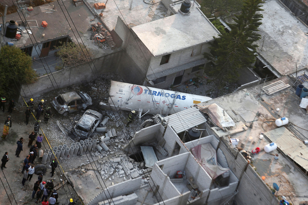 . Aerial view shows emergency responders standing next to a part of a tanker truck after it exploded and landed in a residential area near a highway in the Mexico City suburb of Ecatepec early Tuesday, May 7, 2013.  The blast killed and injured dozens, according to the Citizen Safety Department of Mexico State. Officials did not rule out the possibility the death toll could rise as emergency workers continued sifting through the charred remains of vehicles and homes built near the highway on the northern edge of the metropolis. (AP Photo)