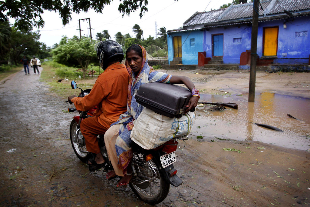 . An Indian couple drives towards a cyclone center, in village Podampeta, in Ganjam district about 200 kilometers  (125 miles) from the eastern Indian city Bhubaneswar, India, Saturday, Oct. 12, 2013. Strong winds and heavy rains pounded India\'s eastern coastline Saturday, as hundreds of thousands of people took shelter from a massive, powerful Cyclone Phailin expected to reach land in a few hours. (AP Photo/Biswaranjan Rout)