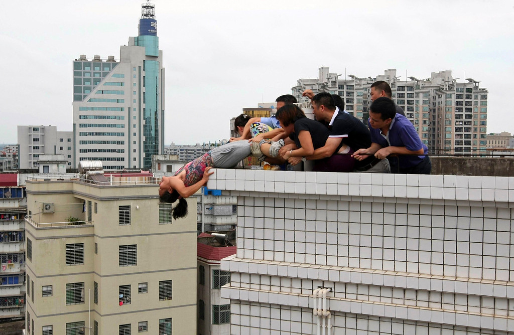 . Rescuers and relatives stop a woman from committing suicide by jumping off a building in Zhanjiang, Guangdong province August 14, 2012. The woman was rescued as she tried to commit suicide after killing her nephew following a family dispute, local media reported. Picture taken August 14, 2012. REUTERS/Stringer