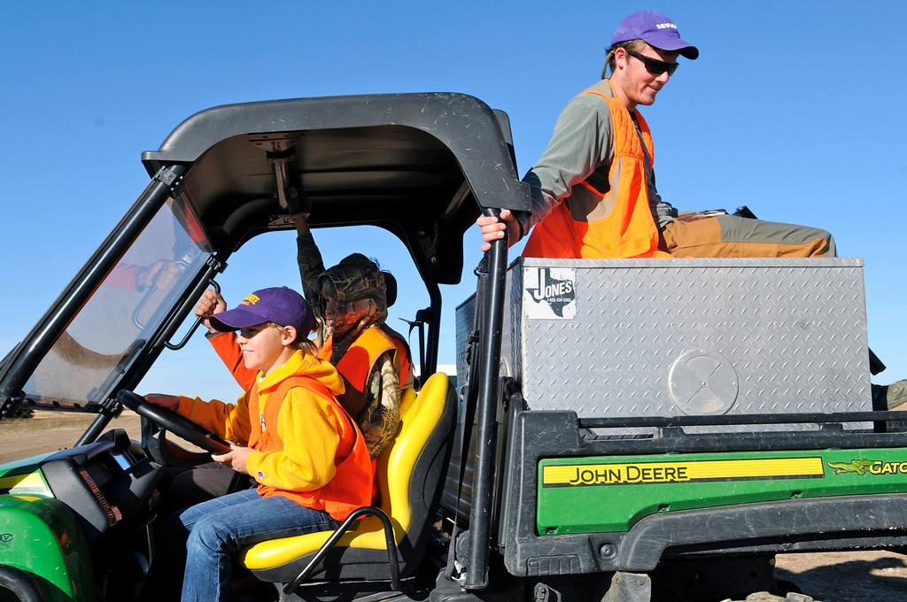 . Denton O\'Neal, right, enjoys the ride as his young cousin John practices his ATV driving skills on his way out to a hunt on the family farm, Saturday, November 9, 2013. Scott Willoughby, The Denver Post