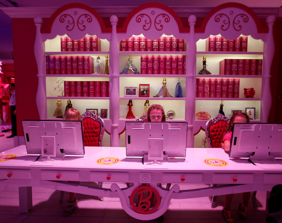 """. Six years old Lara (C) plays with a computer inside a \""""Barbie Dreamhouse\"""" of Mattel\'s Barbie dolls in Berlin, May 16, 2013. The life-sized house, covering about 1,400 square metres offers visitors to try on Barbie\'s clothes in her walk-in closet, tour her living room and her kitchen.   REUTERS/Fabrizio Bensch"""