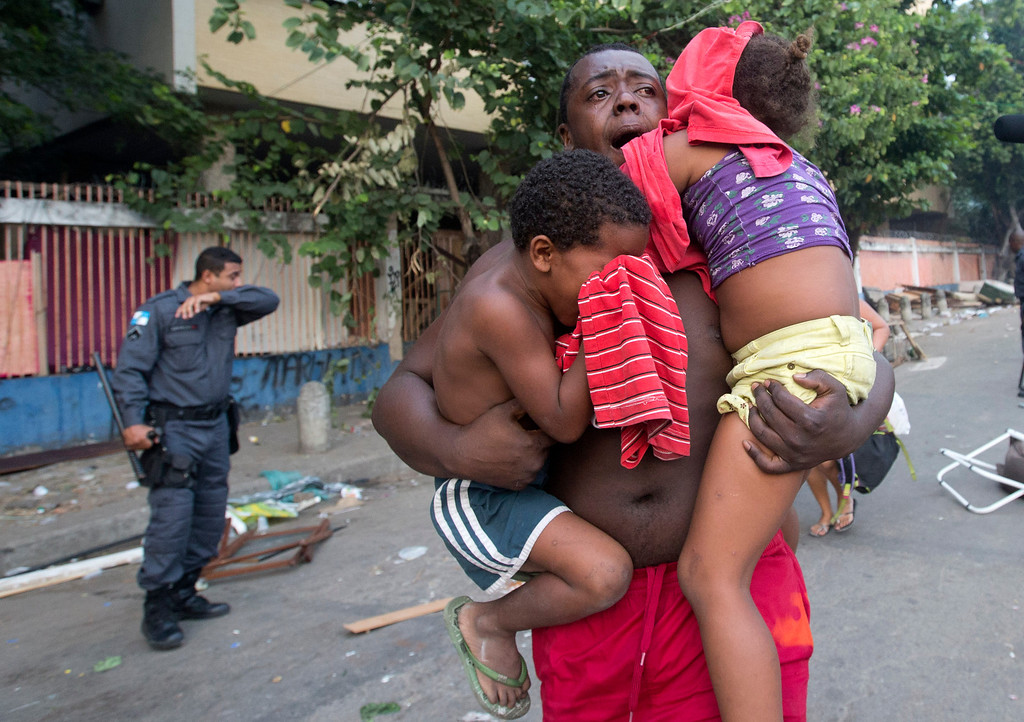 . A man runs while he carries two children during an eviction in Rio de Janeiro, Brazil, Friday, April 11, 2014. Squatters in Rio de Janeiro are clashing with police after a Brazilian court ordered that 5,000 people be evicted from abandoned buildings of a telecommunications company. Officers have used tear gas and stun grenades to try to disperse the families. (AP Photo/Silvia Izquierdo)