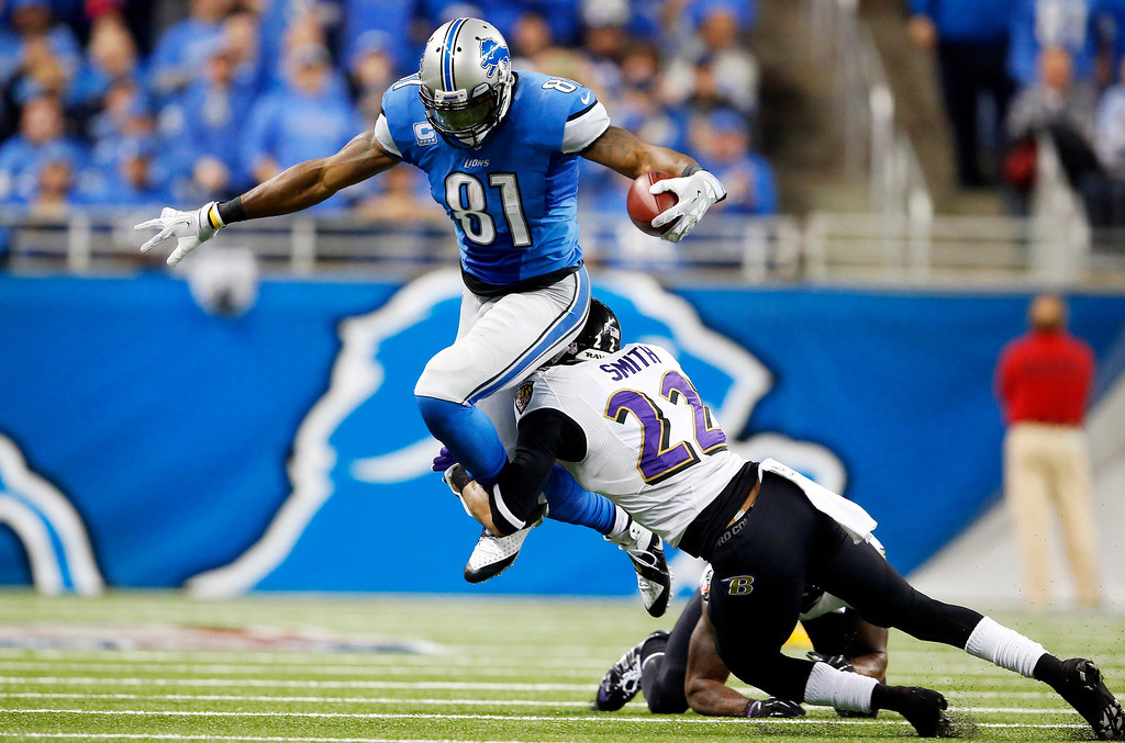 . Baltimore Ravens cornerback Jimmy Smith (22) tackles Detroit Lions wide receiver Calvin Johnson (81) during the third quarter of an NFL football game in Detroit, Monday, Dec. 16, 2013. (AP Photo/Paul Sancya)