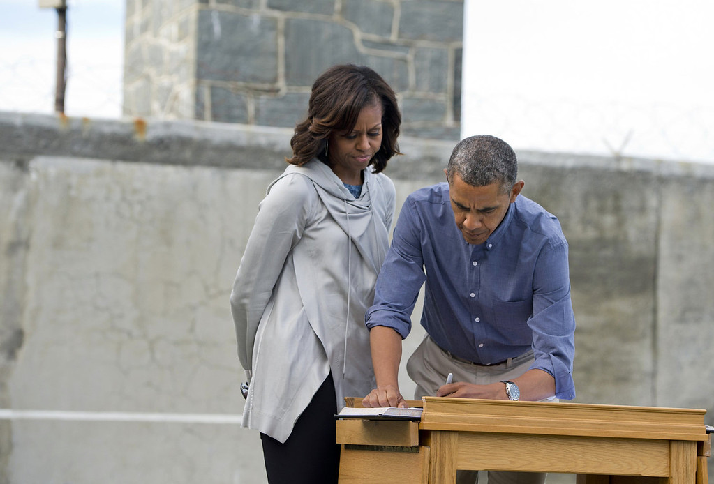 ". US President Barack Obama and First Lady Michelle Obama sign a guestbook in a prison yard as they tour Robben Island outside Cape Town, South Africa, on June 30, 2013. Obama was ""deeply humbled\"" by a visit to the cell where Nelson Mandela spent 18 years as a prisoner, in a solemn homage to the critically ill hero he was unable to see in Pretoria.  SAUL LOEB/AFP/Getty Images"