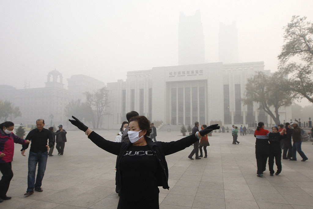 . Local residents dance on a square under heavy smog in Harbin, northeast China\'s Heilongjiang province, on October 21, 2013.   AFP PHOTOSTR/AFP/Getty Images