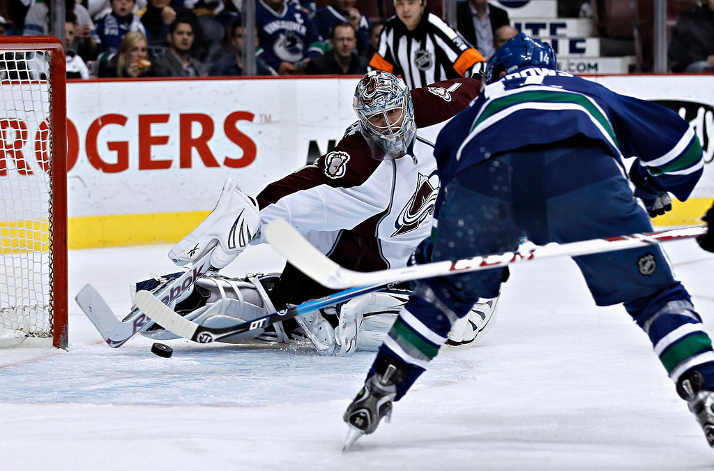 . Vancouver Canucks Alex Burrows (R) scores on Colorado Avalanche goalie Semyon Varlamov during the first period of their NHL hockey game  in Vancouver, British Columbia March 28, 2013.   REUTERS/Andy Clark