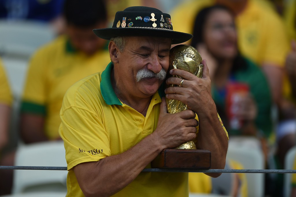 . TOPSHOTS  A Brazil\'s supporter poses with a World Cup trophy replica prior to the quarter-final football match between Brazil and Colombia at the Castelao Stadium in Fortaleza during the 2014 FIFA World Cup on July 4, 2014.     AFP PHOTO / EITAN ABRAMOVICHEITAN ABRAMOVICH/AFP/Getty Images