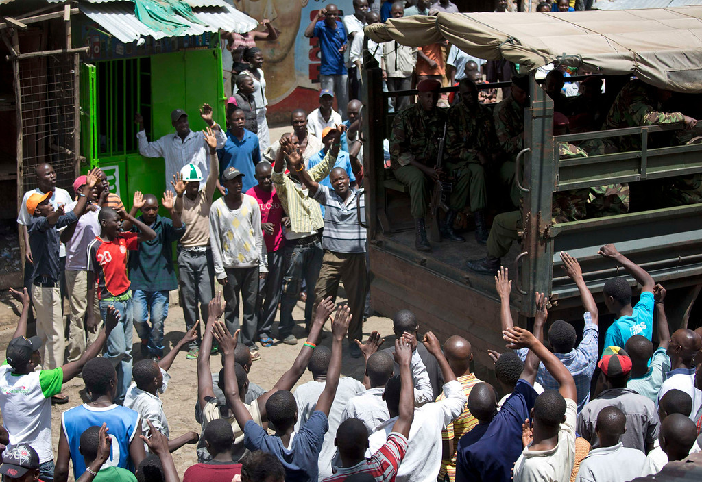 . Supporters of Kenya\'s Prime Minister Raila Odinga wave at the police in the Mathare slum in the Kenyan capital of Nairobi March 9, 2013.  REUTERS/Karel Prinsloo