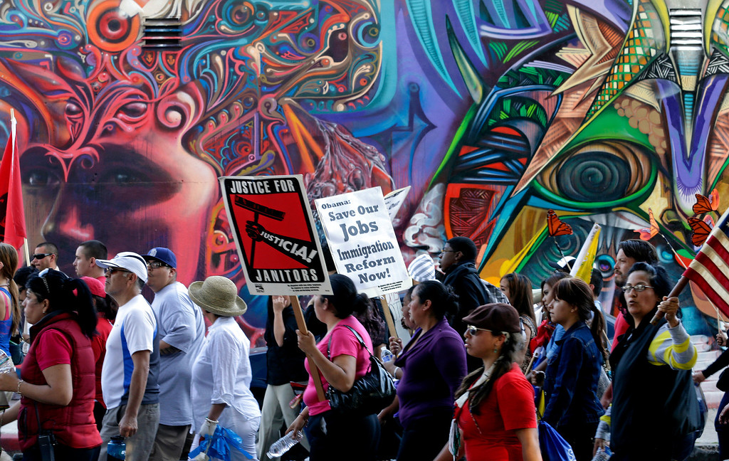 . Marchers pass murals during a May Day rally Wednesday, May 1, 2013, in San Diego. Hundreds of people marched to Chicano Park Wednesday to show support for workers rights and immigration reform. (AP Photo/Gregory Bull)