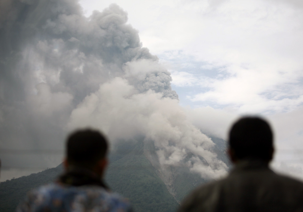 . Villagers watch Mount Sinabung spewing volcanic ash in Tiga Pancur, North Sumatra, Indonesia, Tuesday, Nov. 5, 2013. The 2,600-meter (8,530-foot) -high volcano has been erupting since Sunday, unleashing volcanic ash high into the sky and forcing the evacuation of villagers living around its slope. (AP Photo/Binsar Bakkara)