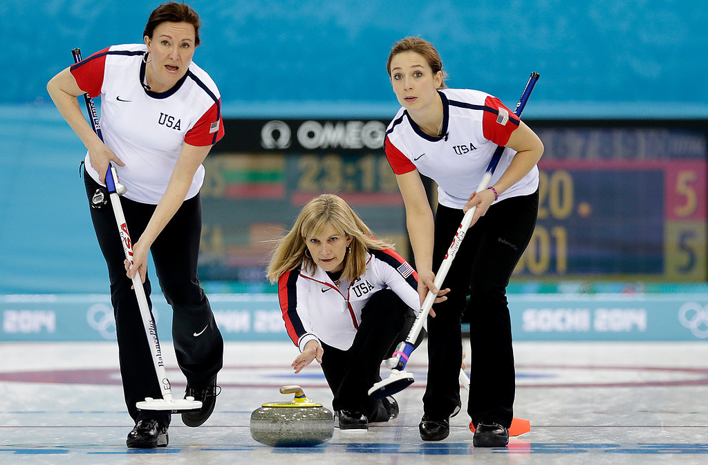 . Erika Brown, center, skip for the United States delivers the rock while Ann Swisshelm, left, and Jessica Shultz, right, prepare to sweep the ice during the women\'s curling competition against Russia at the 2014 Winter Olympics, Tuesday, Feb. 11, 2014, in Sochi, Russia. (AP Photo/Wong Maye-E)