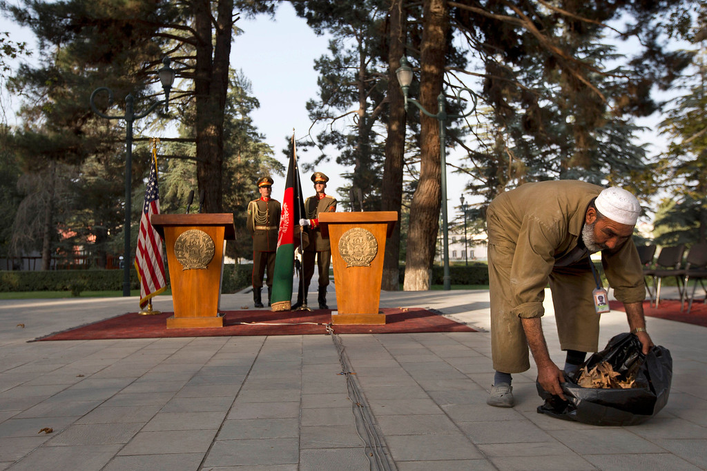 . An employee of the Afghan Presidential Palace clears leaves from the site where U.S. Secretary of State John Kerry and Afghan President Hamid Karzai are expected to speak at a delayed news conference at the palace in Kabul, Afghanistan, on Saturday, Oct. 12, 2013, as a deadline approaches for a security deal about the future of U.S. troops in the country. Karzai and Kerry had a second meeting together at the Presidential Palace during Kerry\'s unannounced visit. The news conference was delayed for extended meetings between the Secretary and President. (AP Photo/Jacquelyn Martin, Pool)