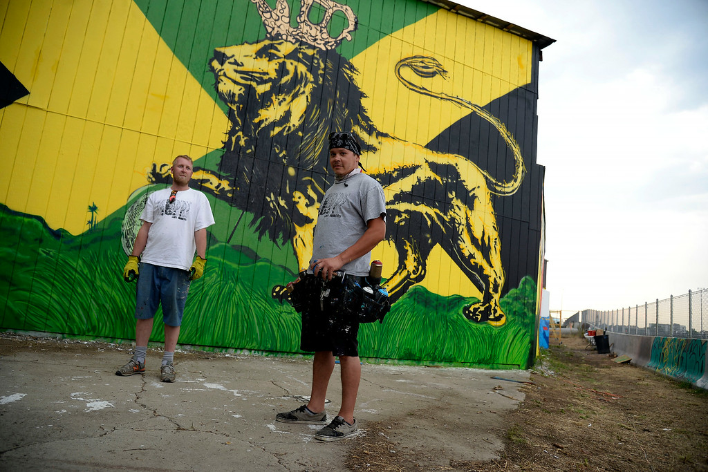 . Jon Lamb (left) and Michael Ortiz of Like Minded Productions work on a large mural outside of the Herbal Cure. The Mural that faces I-25 near the Washington St. and Emerson Street exit was photographed on Tuesday, July 15, 2014. (Photo by AAron Ontiveroz/The Denver Post)