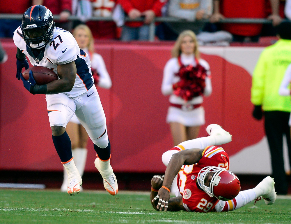 . Knowshon Moreno (27) of the Denver Broncos breaks into the open field on a pass reception after breaking a tackle by Eric Berry (29) of the Kansas City Chiefs during the first half of action at Arrowhead Stadium.  (Photo by AAron Ontiveroz/The Denver Post)