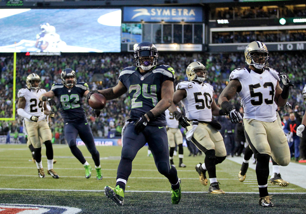 . Seattle Seahawks running back Marshawn Lynch (24) arrives in the end zone with a 31-yard touchdown during the fourth quarter of an NFC divisional playoff NFL football game against the New Orleans Saints in Seattle, Saturday, Jan. 11, 2014. (AP Photo/John Froschauer)