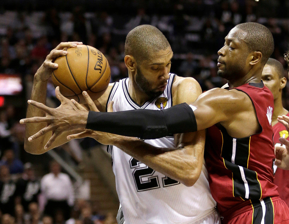 . Miami Heat guard Dwyane Wade, right, defends against San Antonio Spurs forward Tim Duncan during the first half at Game 3 of the NBA Finals basketball series, Tuesday, June 11, 2013, in San Antonio. (AP Photo/Eric Gay)