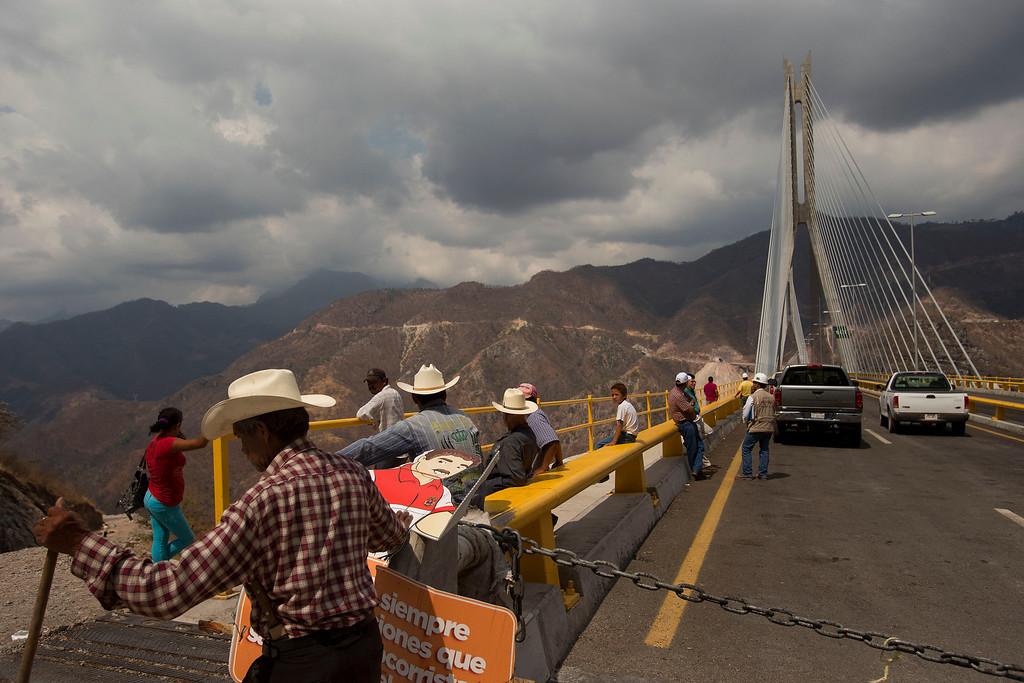 . In this June 11, 2013 photo, workers and residents stand on the recently completed stay-cable bridge called the Baluarte in the western Sierra Madre near Concordia, Mexico. The new highway will cut the drive between Durango and Mazatlan to 2.5 hours from the current six hours of hairpin turns, few guard rails and the Devil\'s Backbone, a stretch of road along the spine of a mountain with several-hundred-foot drops on either side. (AP Photo/Dario Lopez-Mills)