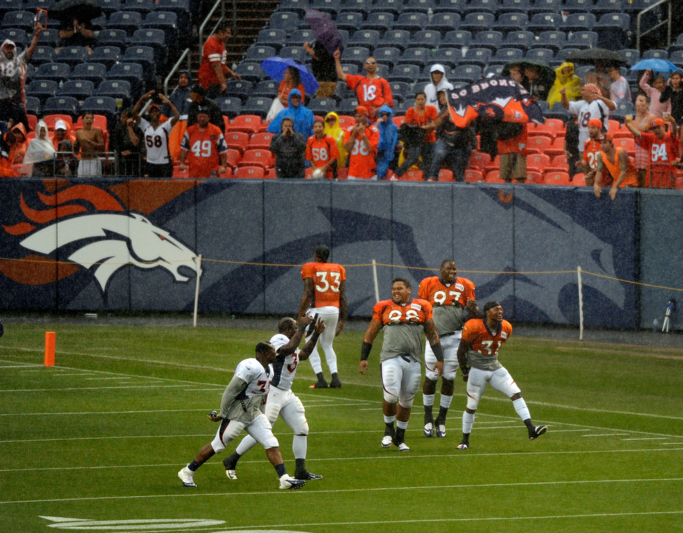 . DENVER, CO. - AUGUST 03: A small group of players drew applause as they ran onto the field during a downpour Saturday night. Denver Broncos fans waited inside Sports Authority Field Saturday night, August 3, 2013 hoping the weather would clear so that the team could practice.  Photo By Karl Gehring/The Denver Post
