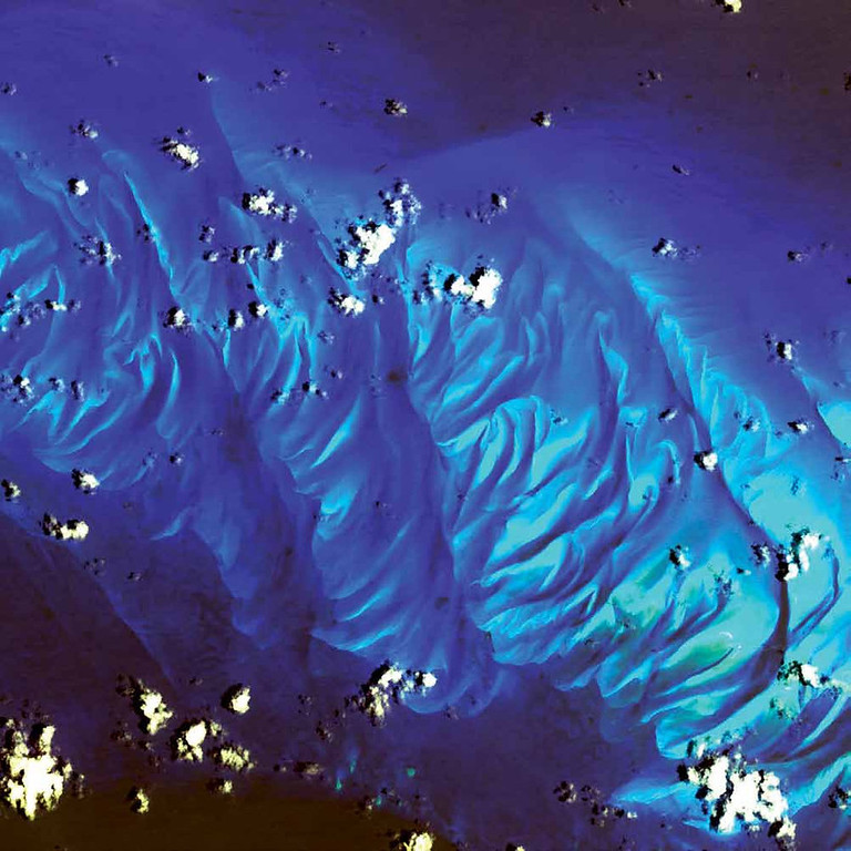 . Carbonate Sand Dunes, Atlantic Ocean In this 2002 Terra image, calcium carbonate sand dunes are apparent in the shallow waters of Tarpum Bay, southwest of Eleuthera Island in the Bahamas. The sand making up the dunes comes from the erosion of limestone coral reefs, shaped into dunes by ocean currents. Eleuthera Island is one of the larger �out� islands of the Bahamas. The island itself consists mainly of low, rounded limestone hills, and the highest elevation of the island is about 60 meters. It has a rough, karst topography with caves, sinkholes, and cenotes. The island is surrounded by coral reefs and pink sand beaches.   NASA