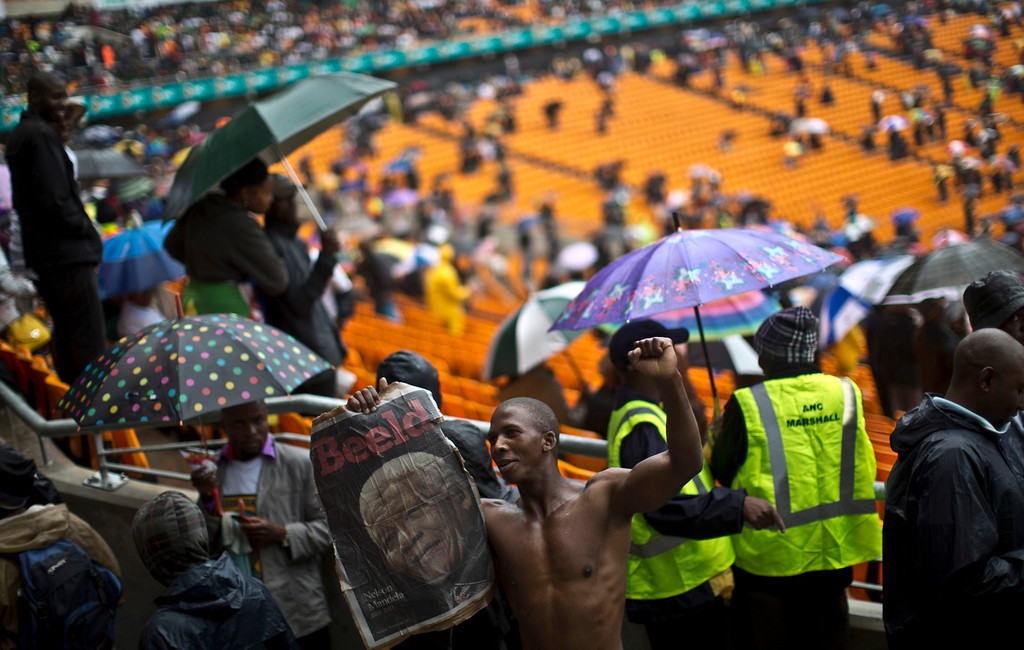. A mourner holding a poster showing Nelson Mandela, bottom, chants slogans during the memorial service for former South African president Nelson Mandela at the FNB Stadium in Soweto near Johannesburg, Tuesday, Dec. 10, 2013. (AP Photo/Muhammed Muheisen)