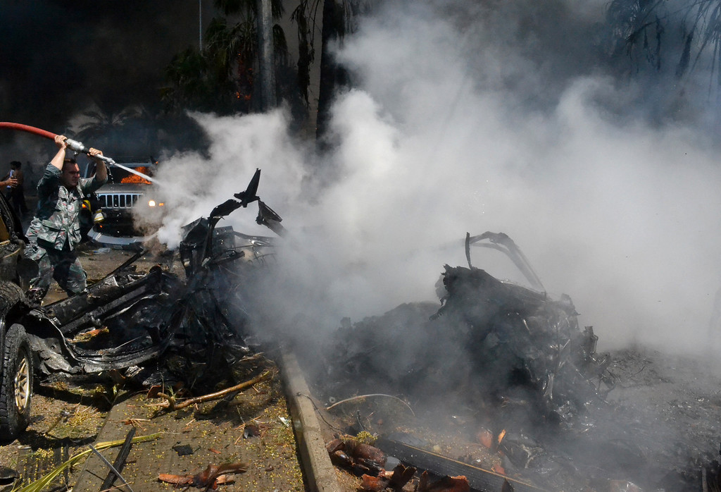 . A Lebanese fire fighter, left, extinguishes a burning car at the site of an explosion outside of a mosque, in the northern city of Tripoli, Lebanon, Friday Aug. 23, 2013. (AP Photo)