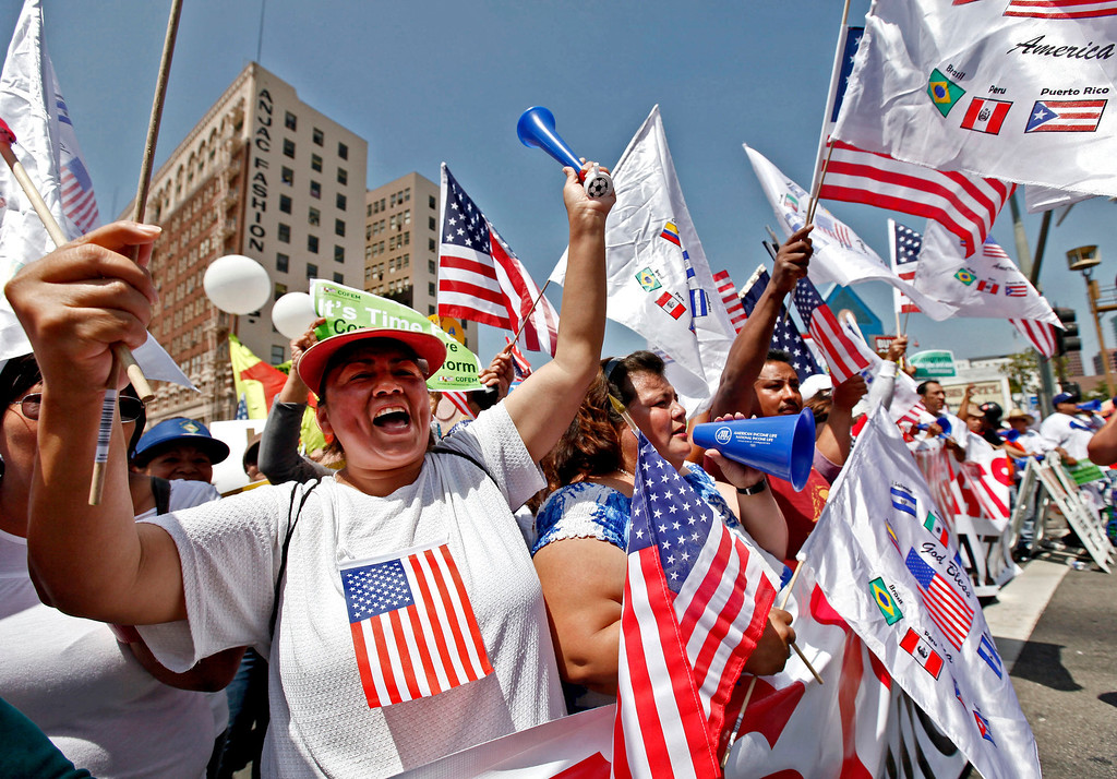 . Alma Banuelos, left, with Emilia Hernandez  shout slogans during a rally in downtown Los Angeles Wednesday, May 1, 2013. In celebration of May Day thousands have gathered for an immigration reform rally in downtown Los Angeles. (AP Photo/Nick Ut)