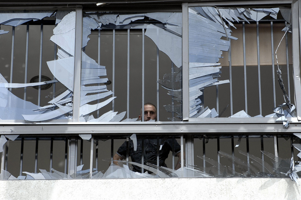 . A man peers through a shattered window at the scene of a bombing in the Beir el-Abed, a southern suburb of Beirut, Lebanon, Tuesday, July 9, 2013. (AP Photo/Ahmed Omar)