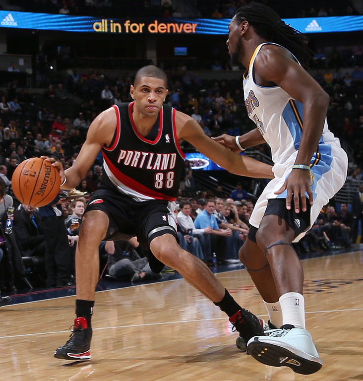 . Portland Trail Blazers forward Nicolas Batum, left, of France, dribbles as Denver Nuggets forward Kenneth Faried covers him in the first quarter of an NBA basketball game in Denver, Tuesday, Feb. 25, 2014. (AP Photo/David Zalubowski)