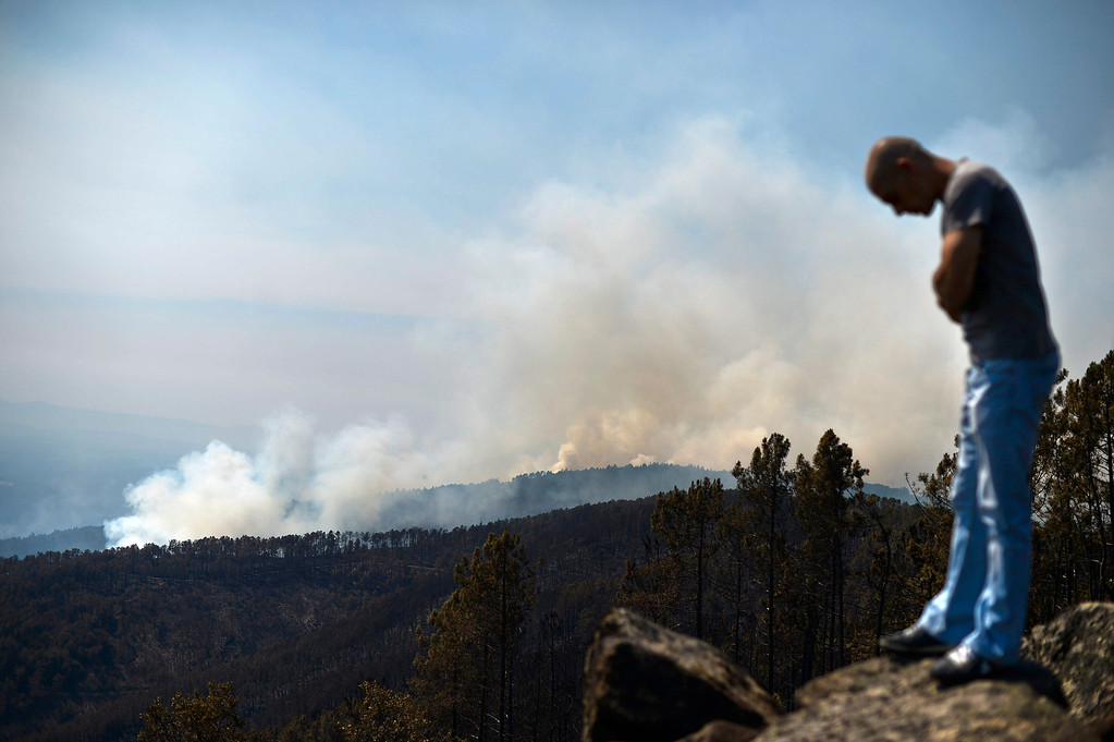. A man stands on top of a hill watching a wildfire burn around Caramulo, central Portugal, on August 30, 2013.    AFP PHOTO / PATRICIA DE MELO MOREIRA/AFP/Getty Images