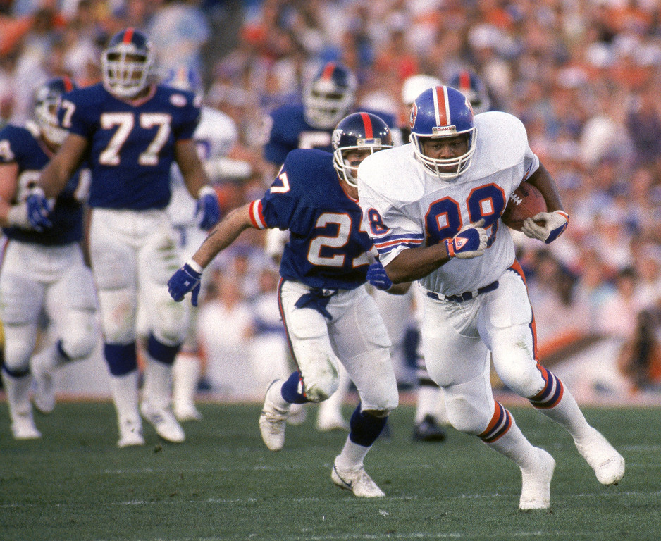 . Tight end Clarence Kay #88 of the Denver Broncos hustles for yards past defensive back Herb Welch #27 of the New York Giants during Super Bowl XXI at the Rose Bowl on January 25, 1987 in Pasadena, California.  The Giants won 39-20.  (Photo by George Rose/Getty Images)