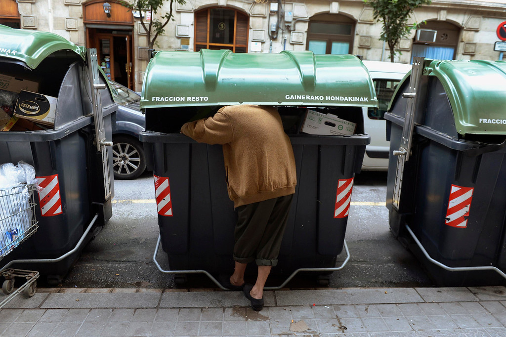 . A man searches for food in a container outside a supermarket in central Bilbao June 12, 2012. The man found an orange and some grapes. According to Caritas, a Catholic church charity, more than eleven million people live below the poverty line in Spain. REUTERS/Vincent West