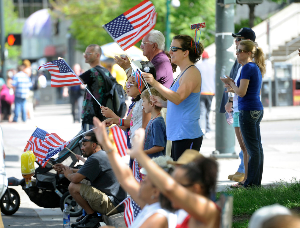 . People wave their flags as the parade makes its way down Broadway. (Photo By Kathryn Scott Osler/The Denver Post)