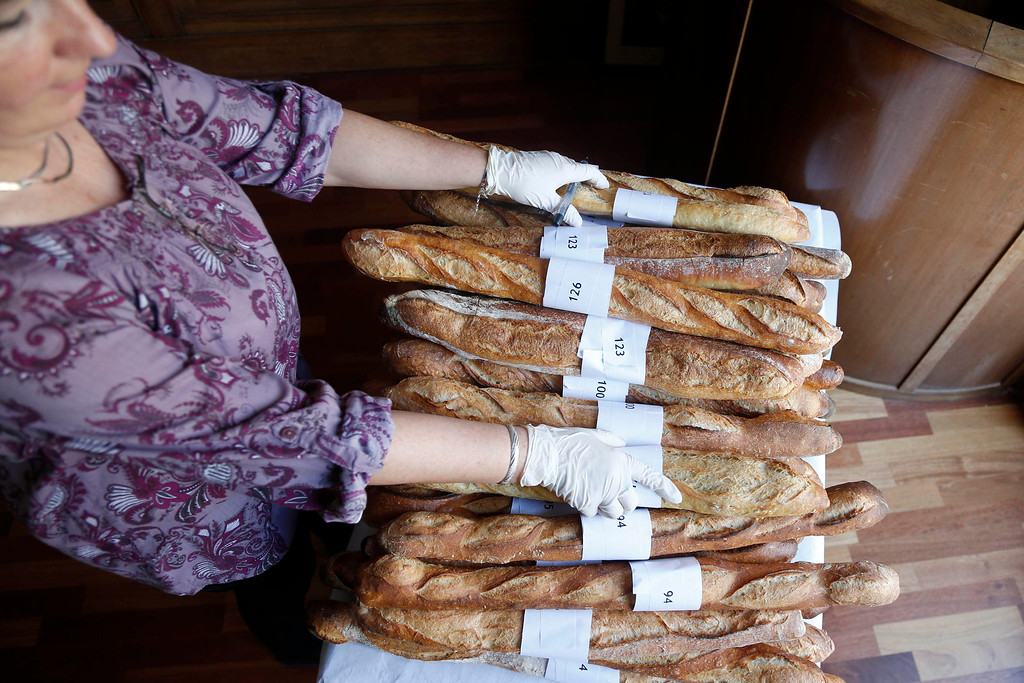 . An assistant stacks baguettes, French bread, which are not selected in the competition for the \'Grand Prix de la Baguette de la Ville de Paris\' (Best Baguette of Paris 2013) annual prize at the Chambre Professionnelle des Artisans Boulangers Patissiers in Paris April 25, 2013. The baguette is a French cultural symbol par excellence and the competition saw 203 Parisian bakers who compete for recognition as finest purveyor of one of France\'s most iconic staples. The baguettes are registered, given anonymous white wrappings and an identification number. They are then carefully weighed and measured to ensure they do not violate the contest\'s strict rules. 52 entries were withdrawn for failing to measure between 55-70cm long or not matching the acceptable weight of between 250-300g. Every year, the winner earns the privilege of baking bread for the French President.   REUTERS/Charles Platiau