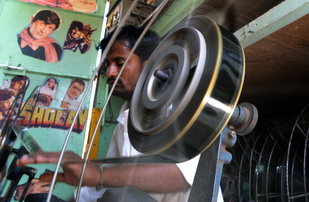 ". Indian cinema projectionist Suhas, winds film roll onto spools inside his ""projection Truck\"" on the premises of the Anup Touring Talkies tent cinema at a ground in central Mumbai on April 20, 2013.  To mark 100 years of Indian Cinema, a Marathi film \""Touring Talkies\"" is being screened in a makeshift tent theatre just like the days of yore, in its pre-multiplex and pre-single screen glory dating back 50 years. The tents, keeping in mind modern audiences, will have plush seating, air conditioning and popcorn and cola alongside fresh sugar-cane juice, roasted groundnuts and gram and pickle and other tit-bits. The cinema will screen four shows per day for a week. The idea of touring talkies was the brainchild of the doyne of Indian cinema, Dadasaheb Phalke, after he saw the British watching movies in tents. The touring cinema would travel through rural India and screen movies in makeshifts tents. At present, one can only find these talkies - whose sweltering tents and basic facilities contrast with the plush, air-conditioned multiplexes springing up in Indian cities, during Jatras (village fairs) in the interiors of the state.  INDRANIL MUKHERJEE/AFP/Getty Images"