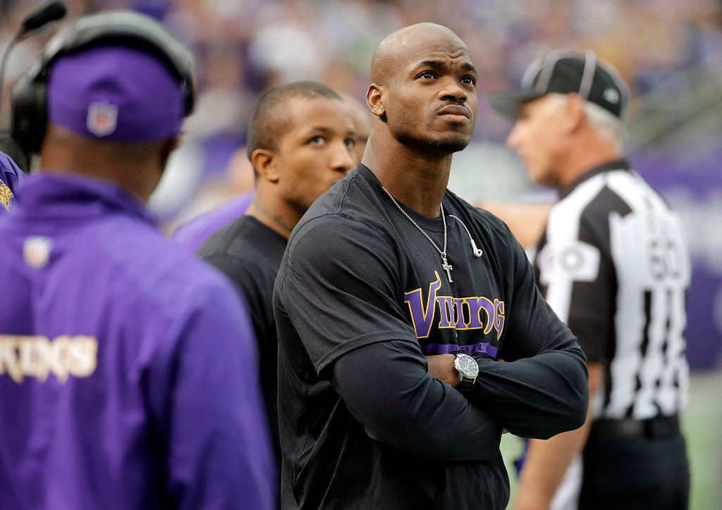 . Injured Minnesota Vikings running back Adrian Peterson stands on the sidelines during the first half of an NFL football game against the Detroit Lions, Sunday, Dec. 29, 2013, in Minneapolis. (AP Photo/Ann Heisenfelt)