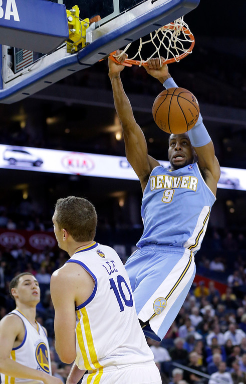 . Denver Nuggets\' Andre Iguodala (9) dunks over Golden State Warriors\' David Lee (10) during the first half of an NBA basketball game in Oakland, Calif., Thursday, Nov. 29, 2012. (AP Photo/Marcio Jose Sanchez)