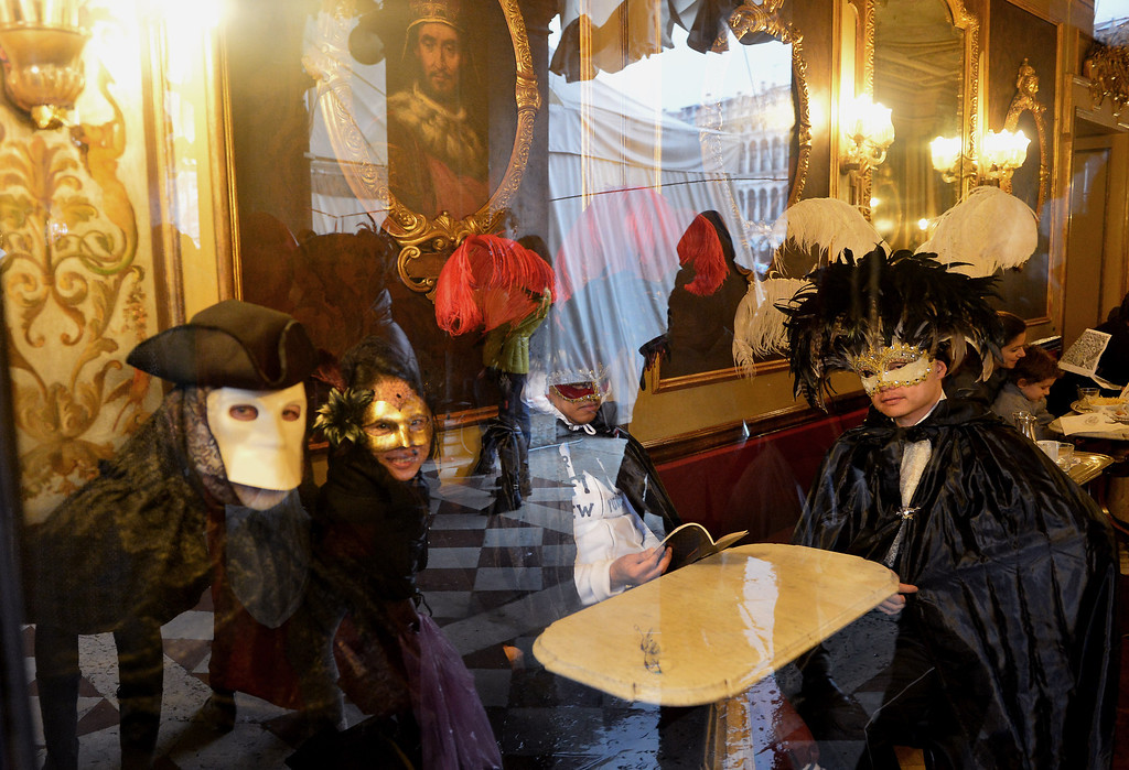 ". Costumed revellers sit at the cafe Florian at St Mark\'s square during the carnival on February 2, 2013 in Venice. The 2013 edition of the Venice carnival is untitled "" Live in Colour\"" and runs from January 26 to February 12.   VINCENZO PINTO/AFP/Getty Images"