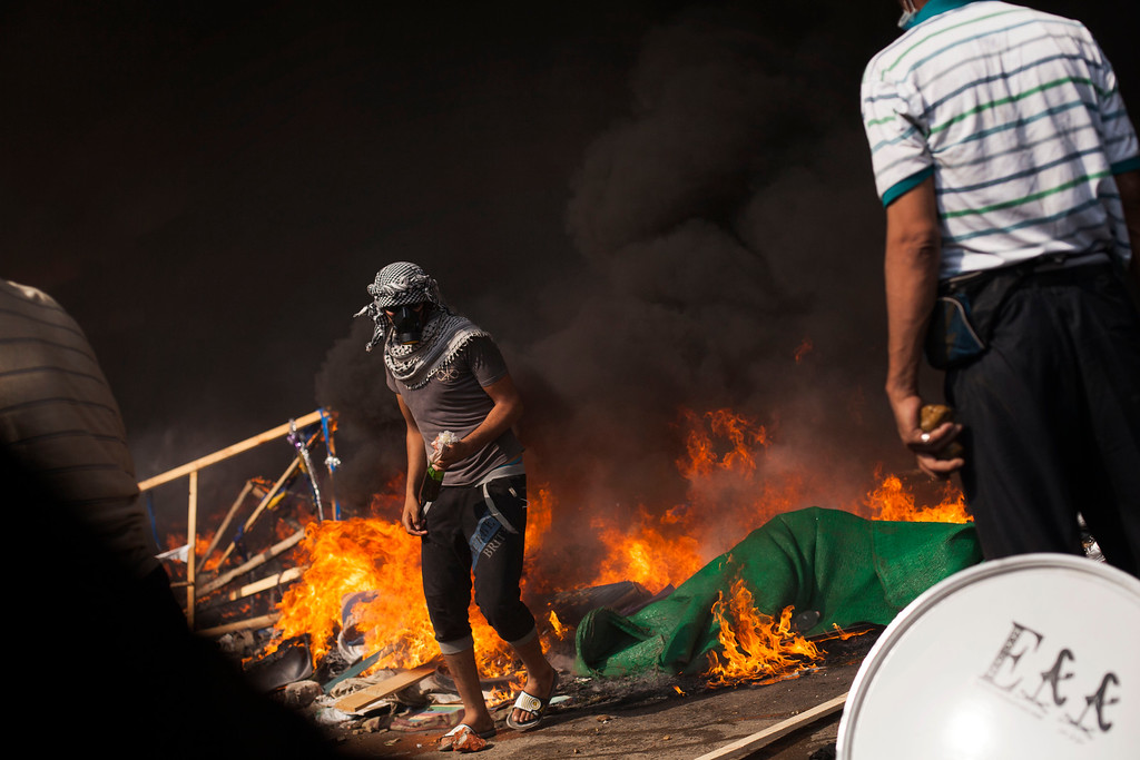 . A supporter of ousted Egyptian President Mohammed Morsi passes a fire barricade carrying a gasoline bomb during clashes against security forces in Cairo\'s Nasr City district, Egypt, Wednesday, Aug. 14, 2013.  (AP Photo/Manu Brabo)