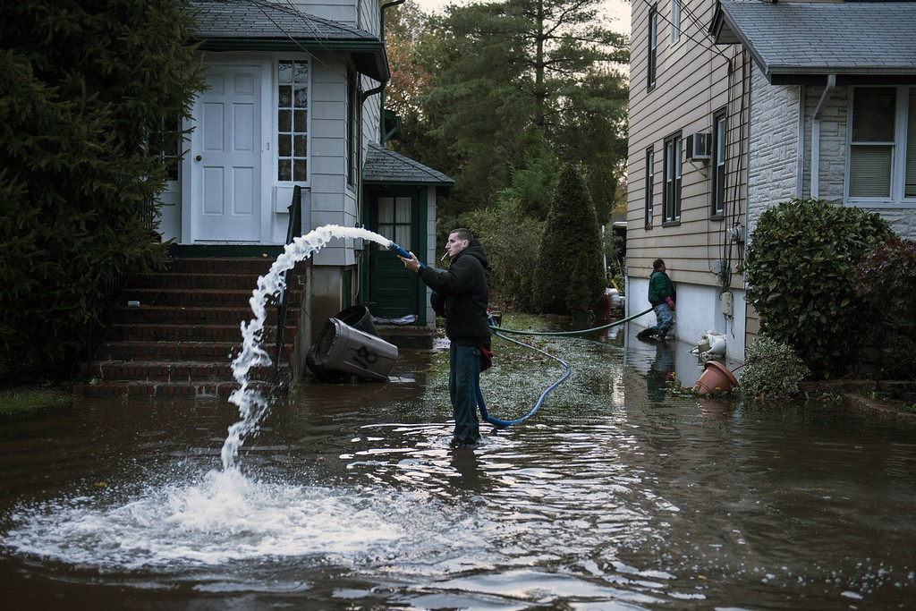 . Rocky Minotti uses a pump to remove ten feet of flood water from his family\'s home October 30, 2012 in Little Ferry, New Jersey.  Hurricane Sandy which hit New York and New Jersey left much of Bergen County flooded and without power.   AFP PHOTO/Brendan SMIALOWSKI
