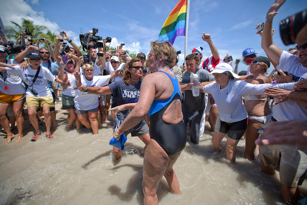 . United States endurance swimmer Diana Nyad is greeted by a crowd as she walks on to the Key West, Fla., shore Monday, Sept. 2, 2013, becoming the first person to swim from Cuba to Florida without the help of a shark cage. Nyad arrived at the beach just before 2 p.m. EDT, about 53 hours after she began her swim in Havana on Saturday. (AP Photo/J Pat Carter)