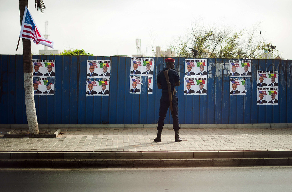 . Security stands guard near a wall covered in posters welcoming US President Barack Obama to Senegal along his motorcade route in Dakar on June 27, 2013.  US President Barack Obama lavished praise on Senegal as a paragon of democracy on Thursday and said it was leading a drive to good governance in Africa. JIM WATSON/AFP/Getty Images