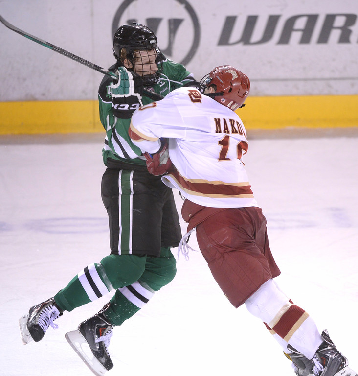 . DENVER, CO. - JANUARY 24:  Denver defenseman David Makowski (10) put a hit on North Dakota wing Derek Rodwell (11) in the third period. The University of Denver hockey team hosted North Dakota at Magness Arena Friday night, January 24, 2014. Photo By Karl Gehring/The Denver Post