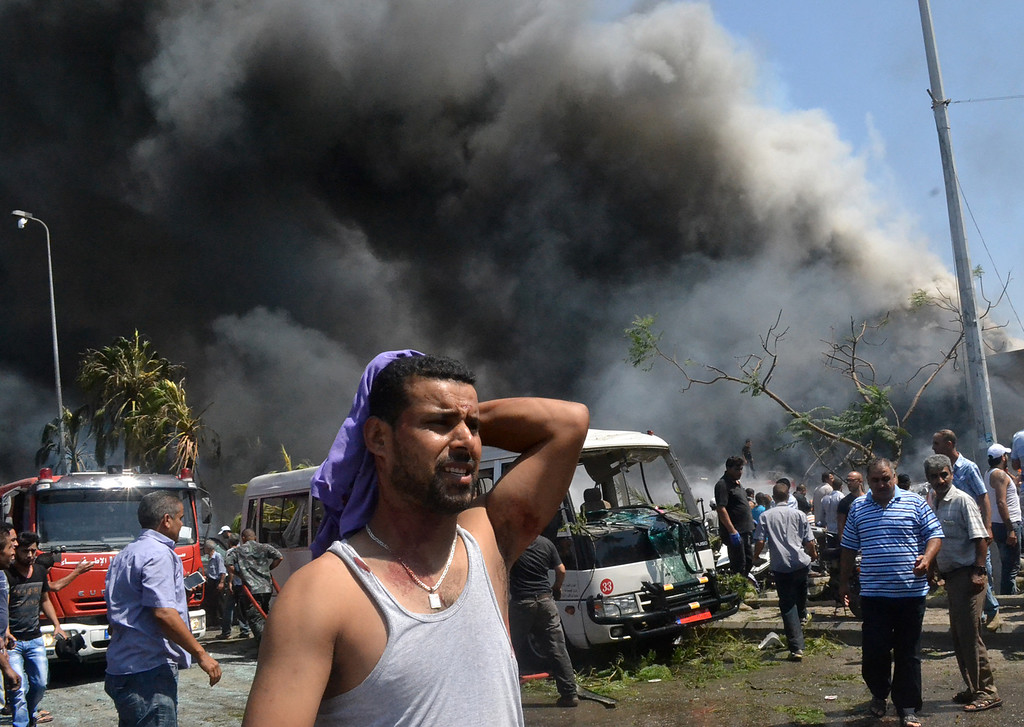 . A Lebanese man reacts at the scene of an explosion in the northern city of Tripoli, Lebanon, Friday Aug. 23, 2013.  (AP Photo)