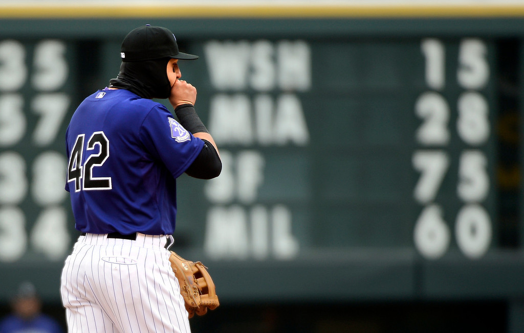 . Troy Tulowitzki of the Colorado Rockies warms up his hand between innings agains the New York Mets April 16, 2013 at Coors Field. Both team wore the number 42 in honor of Jackie Robinson. (Photo By John Leyba/The Denver Post)