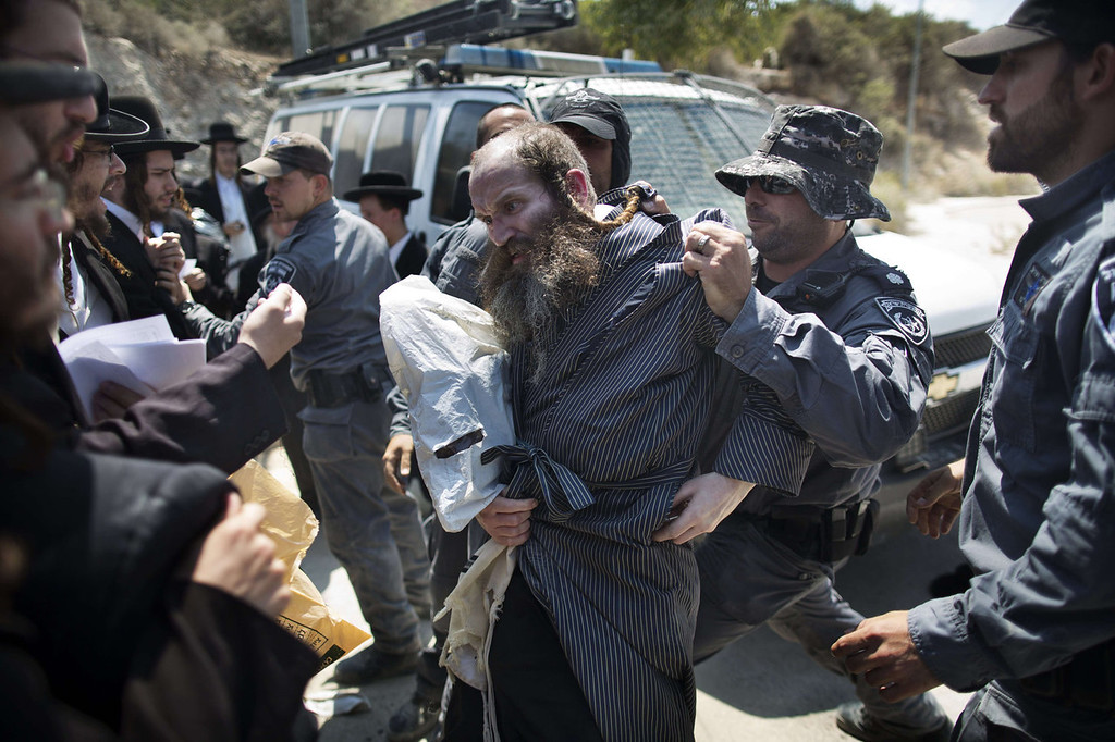 . An Ultra-Orthodox Jewish man is pushed away by an Israeli policeman in Ramat Beit Shemesh West of Jerusalem on August 12 2013, after dozens of Haredim protest against desecration of ancient graves were discovered at a new housing construction site. Some 14 Ultra-orthodox Jews were arrested.   MENAHEM KAHANA/AFP/Getty Images
