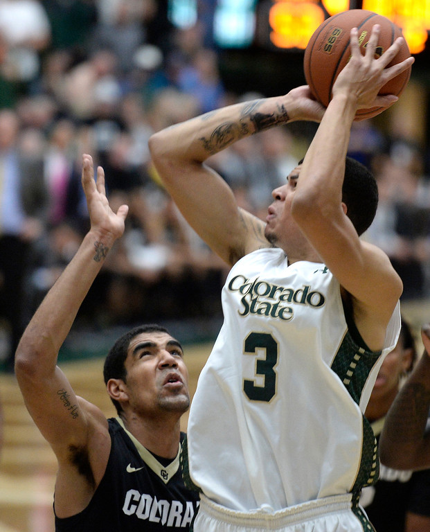 . CSU\'s  Marcus Holt drives to the hoop past Josh Scott during an NCAA game against CU on Tuesday, Dec. 3, 2013, at the Moby Arena in Fort Collins.