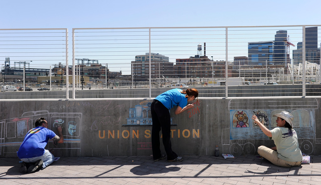 . DENVER, CO.- APRIL 27: Chalk artists from left to right Eric Matelski, Stephanie Andres, and Jennifer Mosquera, draw their interpretations from the day. RTD celebrates the opening of the West line of the light rail with free rides for all and a party atmosphere at many of the stops along the route. Union station had Denver sports team mascots making the rounds as well as live music and food. (Photo By Kathryn Scott Osler/The Denver Post)