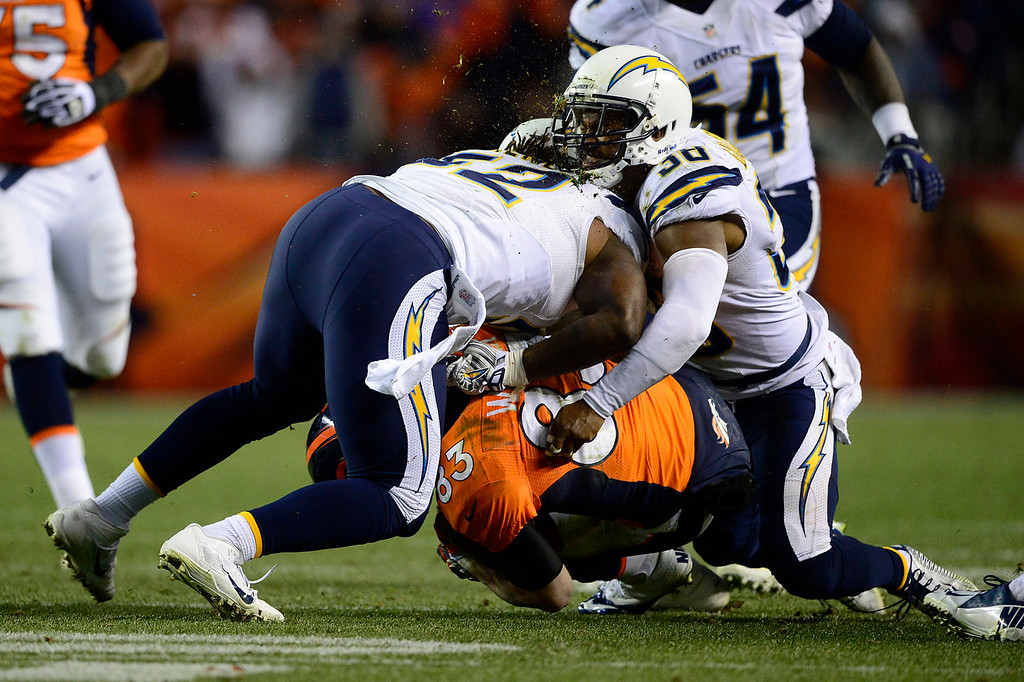 . Denver Broncos wide receiver Wes Welker (83) ducks under a tackle as San Diego Chargers outside linebacker Reggie Walker (52) and San Diego Chargers strong safety Marcus Gilchrist (38) collide in the fourth quarter. The Denver Broncos take on the San Diego Chargers at Sports Authority Field at Mile High in Denver on January 12, 2014. (Photo by AAron Ontiveroz/The Denver Post)