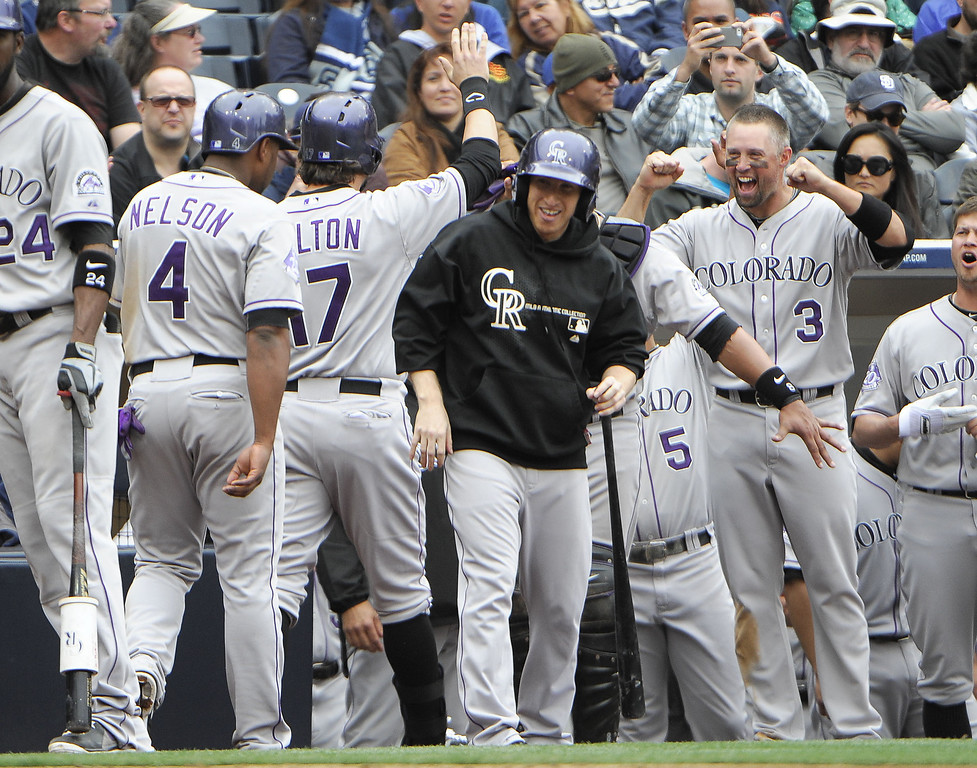 . Todd Helton #17 of the Colorado Rockies is congratulated after he hit a two-run homer during the seventh inning of a baseball game against the San Diego Padres at Petco Park on April 14, 2013 in San Diego, California.  The Rockies won 2-1.  (Photo by Denis Poroy/Getty Images)