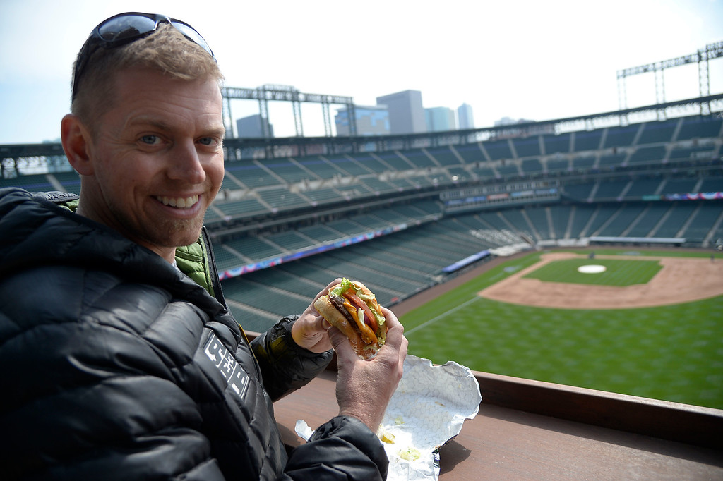 . Jason Rogers shows off the Chub Burger from high above Coors Field April 2, 2014 as they get ready for opening day. Chubs burgers can be found up on The Rooftop, where the Rockies took out the right field upper decks to create the scenic view of downtown Denver. They removed about 3500 seats to make way for the Rooftop. (Photo by John Leyba/The Denver Post)